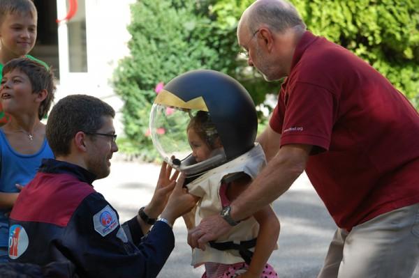 A. Soucek & G. Grömer helfen einem Kind beim Anziehen des Kinderraumanzuges